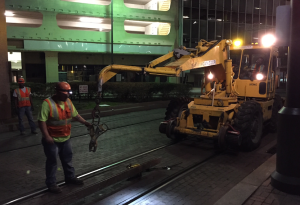 Rail is about to be hoisted out of the ground to be cut into smaller segments and removed from the scene.