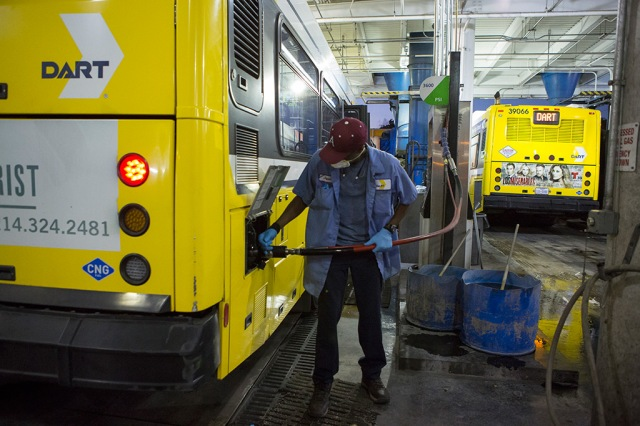A DART employee fills a bus with compressed natural gas at the East Dallas bus depot.
