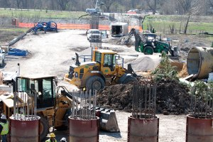 Heavy equipment clears dirt and levels the ground south of Ledbetter Station.