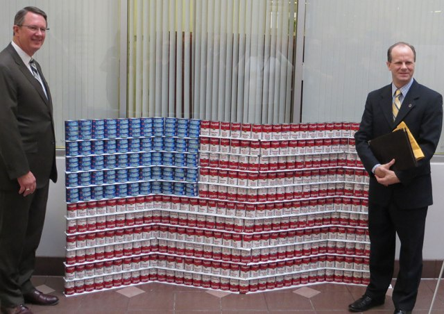 DART President/Executive Director Gary Thomas (left) poses with Union Gospel Mission Director of Development and Public Relations Jeff Steed in front of a canned food flag created by DART's procurement department.