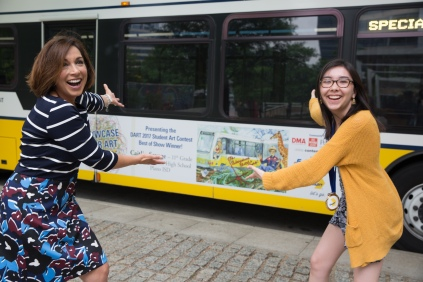DART's 2017 Student Art Contest best of show winner, Caitlin Savage strikes a pose with NBC 5 news anchor Deborah Ferguson next to a bus featuring Savage's artwork at the DMA ceremony Saturday. Savage created her piece as an eleventh-grader from Plano East Senior High School in Plano ISD.